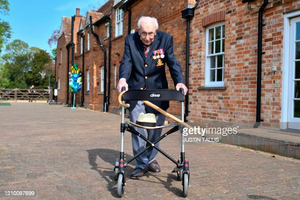 British World War II veteran Captain Tom Moore poses with his walking frame doing a lap of his garden in the village of Marston Moretaine, 50 miles...
