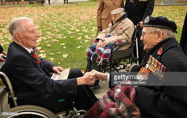 British World War One veterans Bill Stone and Harry Patch shake hands as Henry Allingham looks on before the start of Armistice day commemorations in...