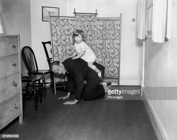 British writer Alan Alexander Milne entertains his son Christopher Robin Milne in the nursery where Winnie the Pooh was born in his country home...