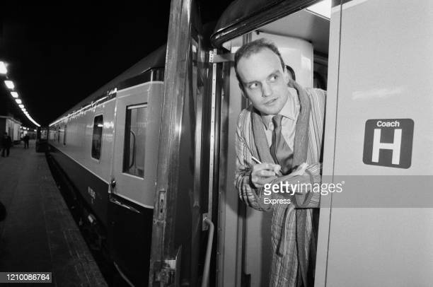 British writer and journalist Nicholas Coleridge wearing a dressing gown as he writes in a note book standing in the open door of a railway carriage...
