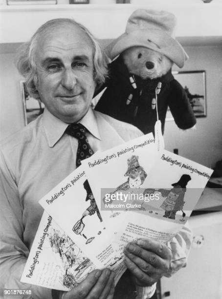 British writer Michael Bond author of the Paddington Bear books holds the four winning paintings in Paddington's Painting Competition at his office...