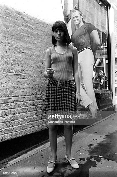 A British young woman wearing an optical miniskirt posing in front of John Stephen's clothes shop 'Trecamp' She has an asymmetric haircut launched by...