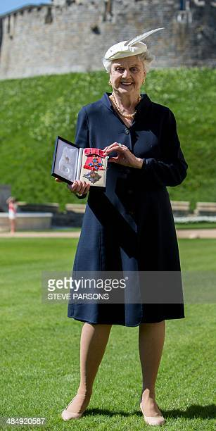 BritishAmerican actress Angela Lansbury poses for photographs after she was promoted to Dame Commander of the Order of the British Empire by Queen...