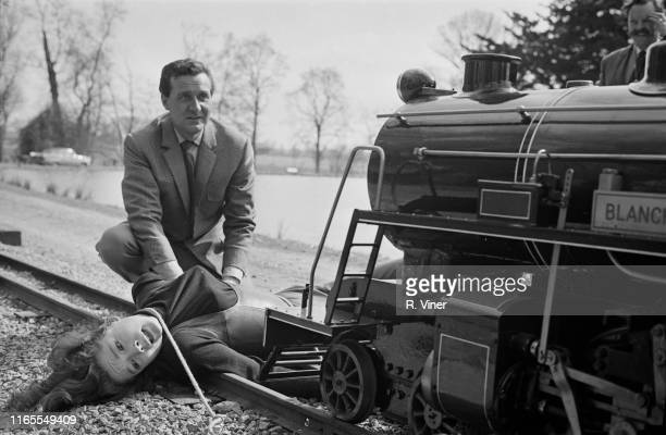 British-American actress Patrick Macnee with English actress Diana Rigg tied to the rail of a train filming a scene of television series 'The...