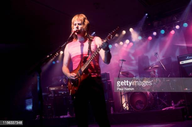 BritishAmerican comedian Christopher Guest in costume as British musician Nigel Tufnel of the group Spinal Tap plays guitar as he performs onstage...