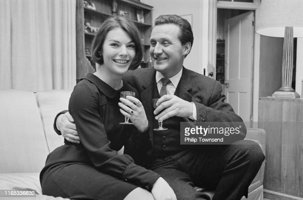 British-American film and television actor Patrick Macnee and English film and television actress Katherine Woodville , holding wine glasses, UK,...