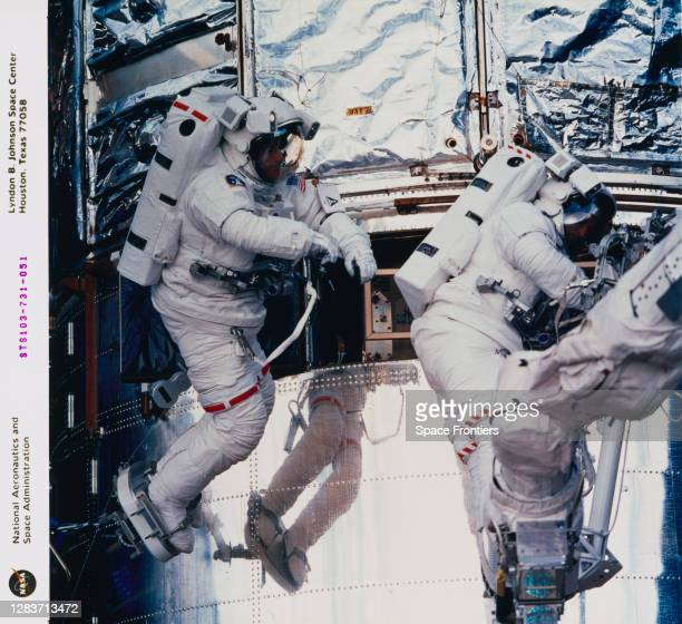 British-American NASA astronaut C Michael Foale and Swiss ESA astronaut Claude Nicollier replacing one of the Fine Guidance Sensors of the Hubble...