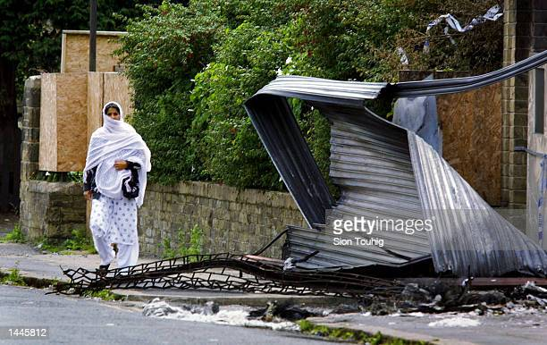 BritishAsian woman walks past wreckage in the Manningham district of Bradford the site of recent rioting caused by tension between the local Asian...