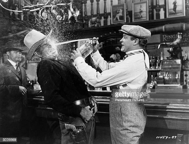 Britishborn actor and comedian Bob Hop sprays water in the face of American actor Bruce Cabot in a saloon in a still from director George Marshall's...