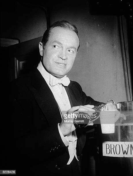 Britishborn actor and comedian Bob Hope pours himself a cola from a bottle backstage at the Academy Awards where he was a presenter RKO Theater Los...