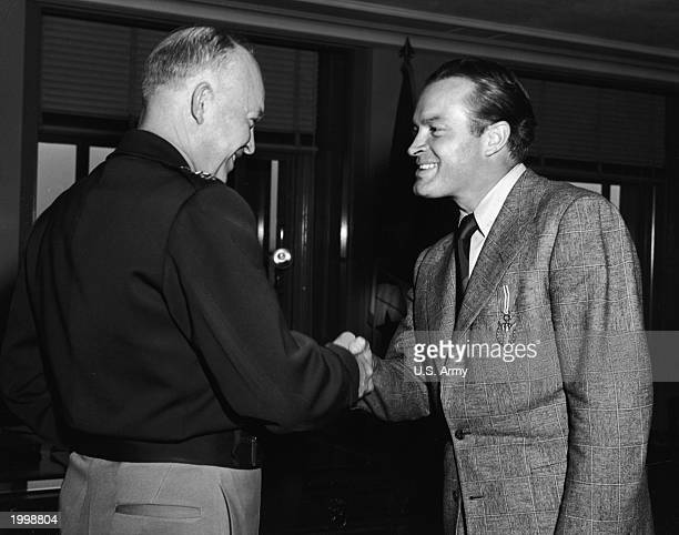 Britishborn actor and comedian Bob Hope shakes hands with General Dwight D Eisenhower after receiving a Medal of Merit for his work as a USO...
