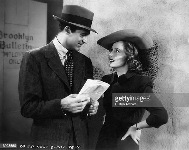 Britishborn actor Cary Grant holds a folded newspaper and looks at American actor Irene Dunne while they stand outside the employee's entrance of the...