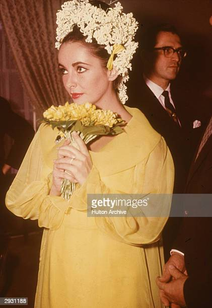 Britishborn actor Elizabeth Taylor a yellow dress and floral headdress holds a bouquet of flowers at her wedding to actor Richard Burton March 15 1964