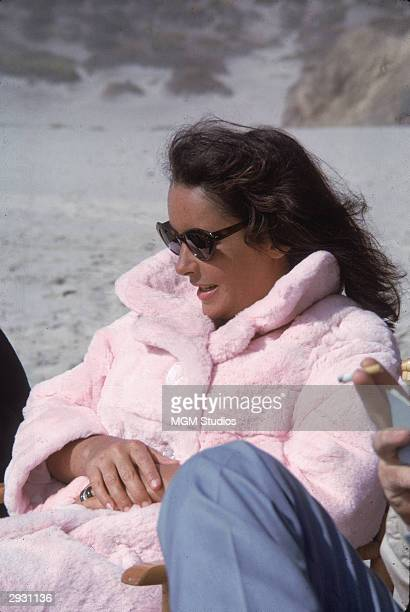 Britishborn actor Elizabeth Taylor in a furry pink coat with oversized buttons sits and rests while on the set of 'The Sandpiper' directed Vincente...