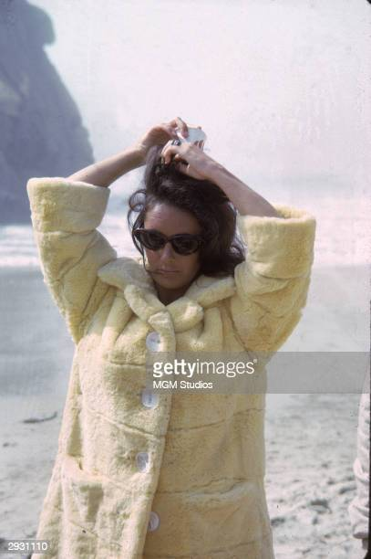 Britishborn actor Elizabeth Taylor in a furry yellow coat with oversized buttons adjusts her hair while on the set of 'The Sandpiper' directed...
