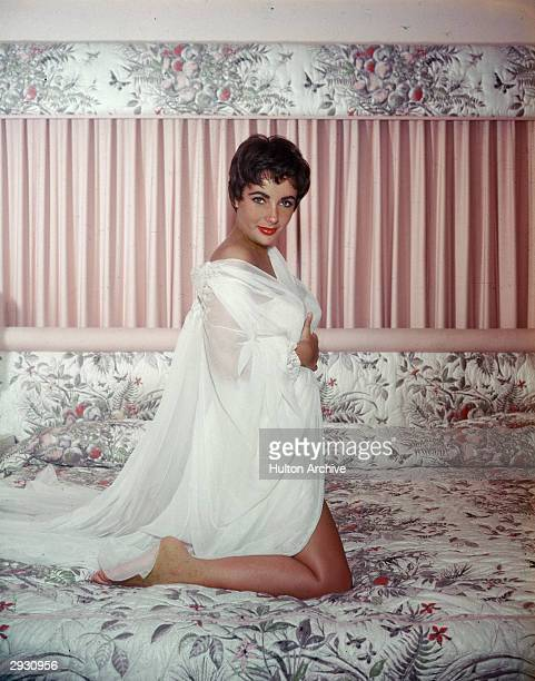 British-born actor Elizabeth Taylor kneels on a bed and wears a sheer white nightgown and robe, circa 1950s.