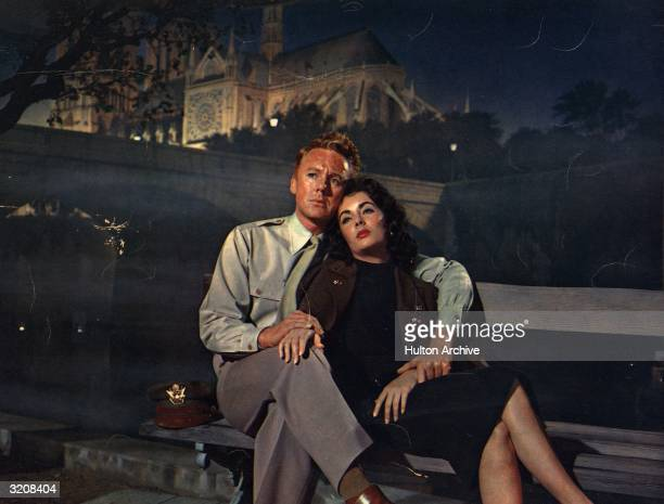 Britishborn actor Elizabeth Taylor leans against American actor Van Johnson wearing his military jacket sitting on a bench in front of a backdrop of...
