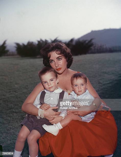 Britishborn actor Elizabeth Taylor sits in a red evening dress with her sons Michael and Christopher Wilding on her lap mid 1950's