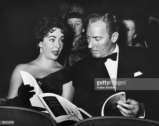Britishborn actor Elizabeth Taylor talks with her second husband British actor Michael Wilding while sitting in the audience for the premiere of...