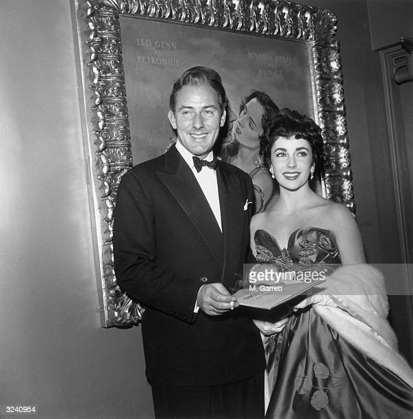Britishborn actor Elizabeth Taylor wearing an evening gown with a fur coat stands next to her soontobe second husband English actor Michael Wilding...
