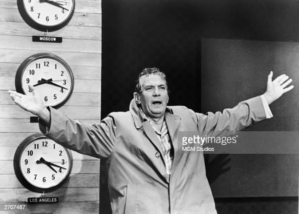 Britishborn actor Peter Finch wears a raincoat and raises his arms in a still from the film 'Network' directed by Sydney Lumet 1976