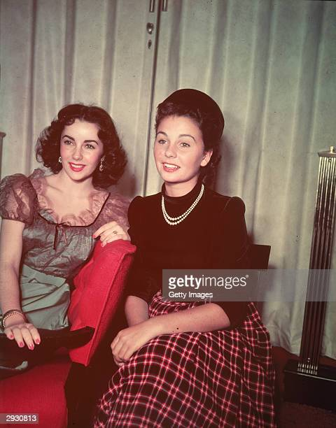 Britishborn actors Elizabeth Taylor and Jean Simmon sit together and smile circa 1940s