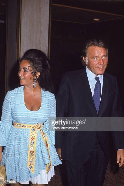 British-born actress Elizabeth Taylor and her husband, Welsh-born actor Richard Burton , hold hands as they speak to the press at the 7th Annual...