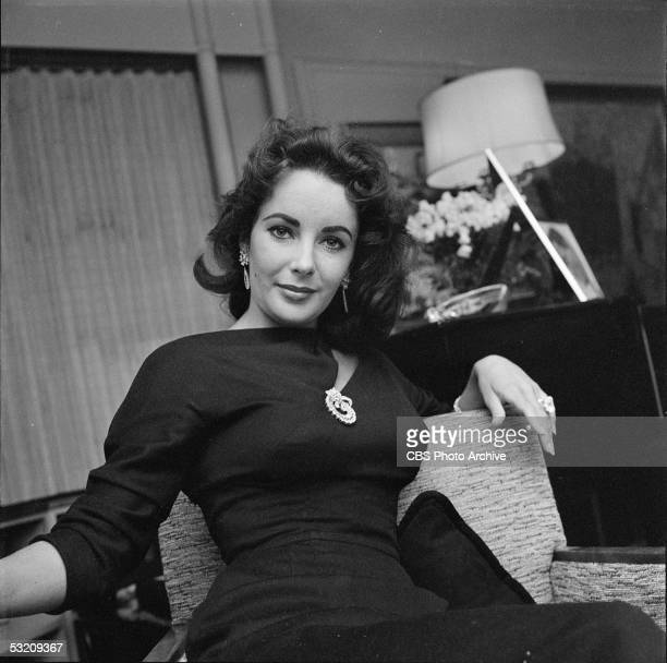 Britishborn actress Elizabeth Taylor poses her arm over the back of her chair in her home Berverly Hills California February 20 1957 She is wearing a...