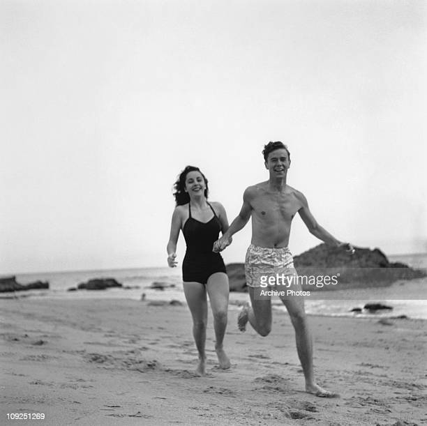 Britishborn actress Elizabeth Taylor runs along a beach with her friend actor Marshall Thompson circa 1948