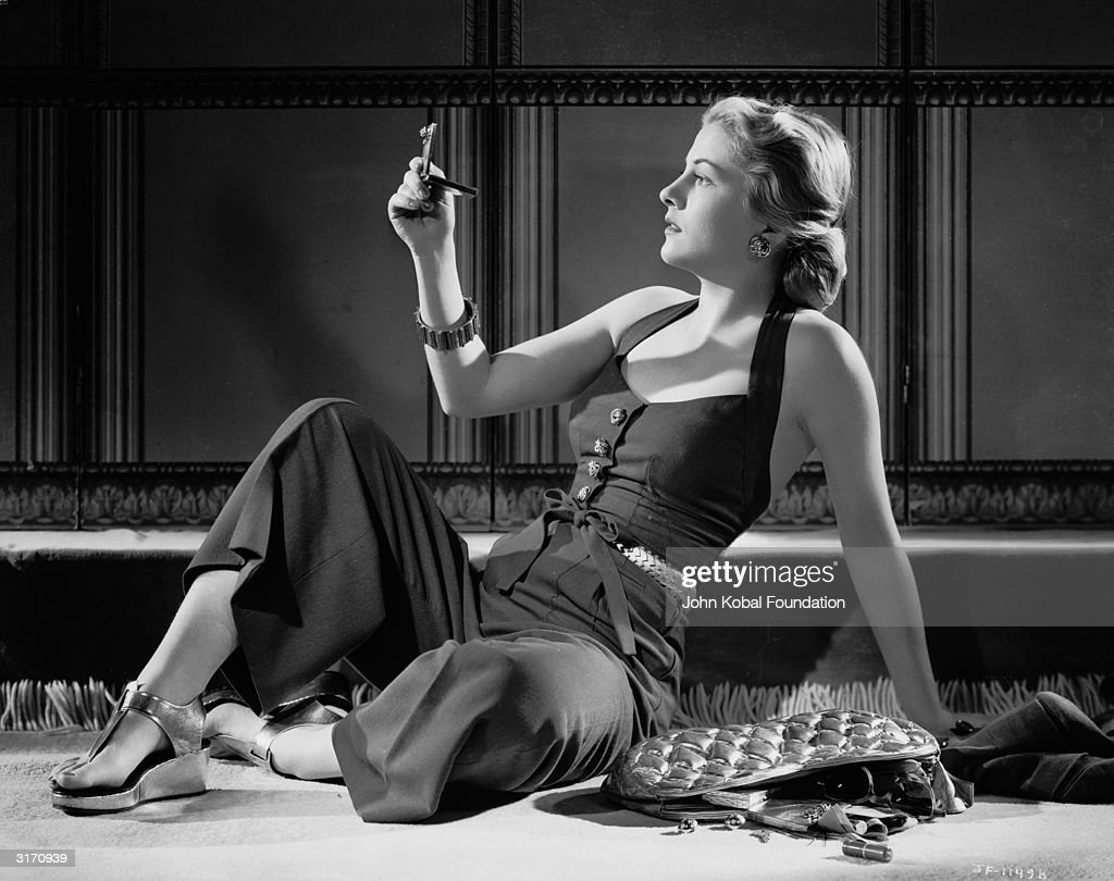 British-born actress Joan Fontaine checks her reflection in a pocket mirror, while the contents of her handbag spill out onto the ground next to her.