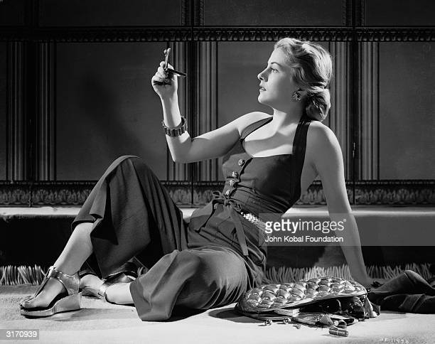 Britishborn actress Joan Fontaine checks her reflection in a pocket mirror while the contents of her handbag spill out onto the ground next to her