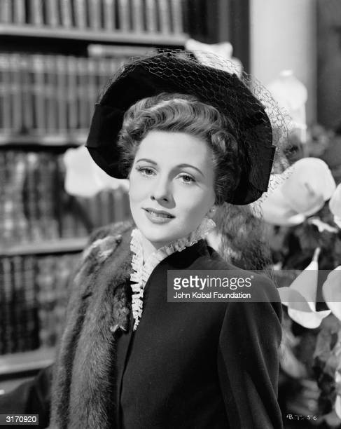 Britishborn actress Joan Fontaine wearing a hat with a veil and a fur stole over one shoulder in her role as Lina McLaidlaw Aysgarth in 'Suspicion'...