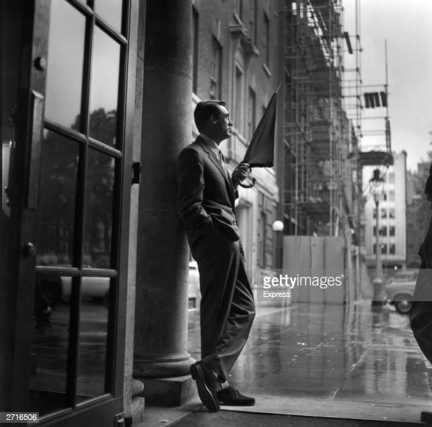Britishborn American actor Cary Grant sheltering in a hotel porch as he waits for the rain to stop Circa 1957