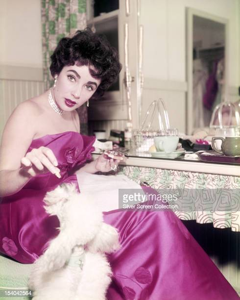 Britishborn American actress Elizabeth Taylor feeding tidbits from her table to a pet poodle circa 1955