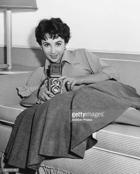 Britishborn American actress Elizabeth Taylor holding a Rolleiflex twinlens reflex camera USA 1953
