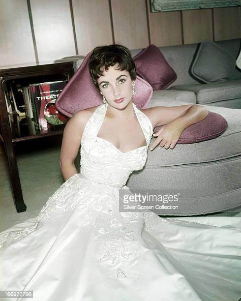 British-born American actress Elizabeth Taylor in a full length, white satin dress, 1954.