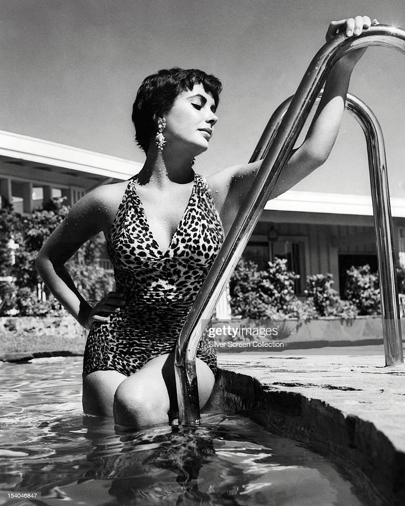 British-born American actress Elizabeth Taylor (1932 - 2011) in a swimming pool, wearing a one-piece, leopard print swimsuit, circa 1955.