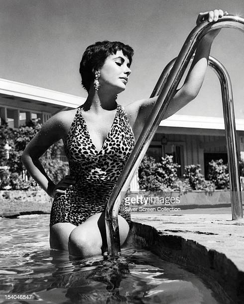 Britishborn American actress Elizabeth Taylor in a swimming pool wearing a onepiece leopard print swimsuit circa 1955