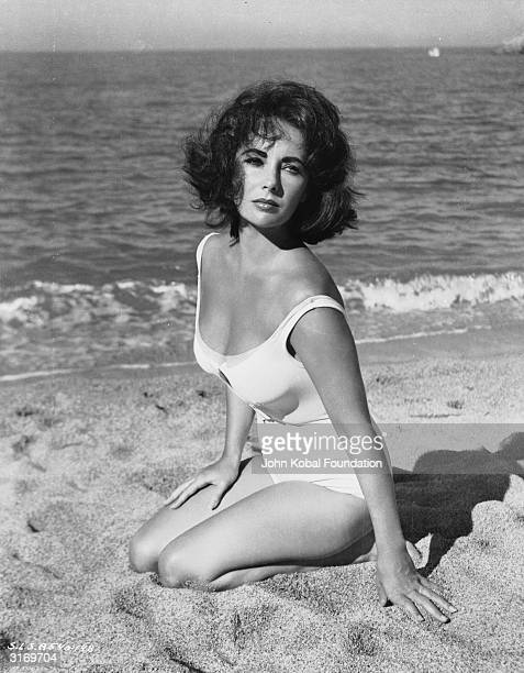 Britishborn American actress Elizabeth Taylor kneeling on the beach during the filming of Tennessee Williams' 'Suddenly Last Summer' directed by...