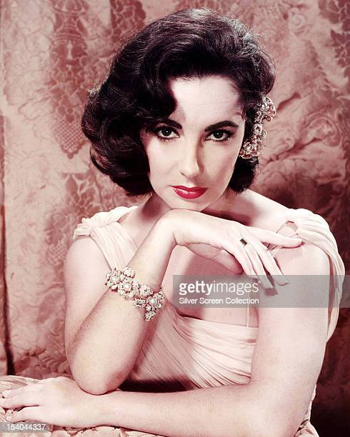 British-born American actress Elizabeth Taylor , wearing an evening gown and a pearl bracelet, circa 1955.