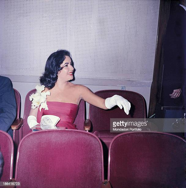 Britishborn American actress Elizabeth Taylor wearing white gloves and an evening dress attending the presentation of the film Around the World in 80...