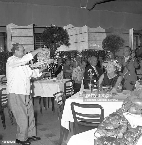 Britishborn American actress Jean Fontaine smiling while looking at the Alfredo's restaurant wellknown fettuccine Rome 1956