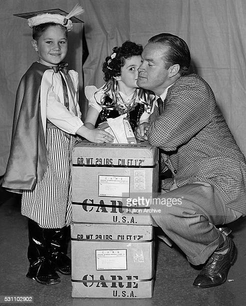 Britishborn American Bob Hope poses with a pair of costumed children and two CARE boxes Poland 1940s or 1950s CARE was a humanitarian agency its...