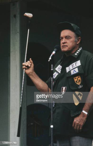 British-born American comedian Bob Hope holding a driver on stage as he performs for the GIs on Christmas Day at Long Binh Post in Long Binh,...