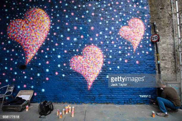 Britishborn Australian artist James Cochran known as 'Jimmy C' puts the finishing touches to a mural to commemorate the victims of the London Bridge...