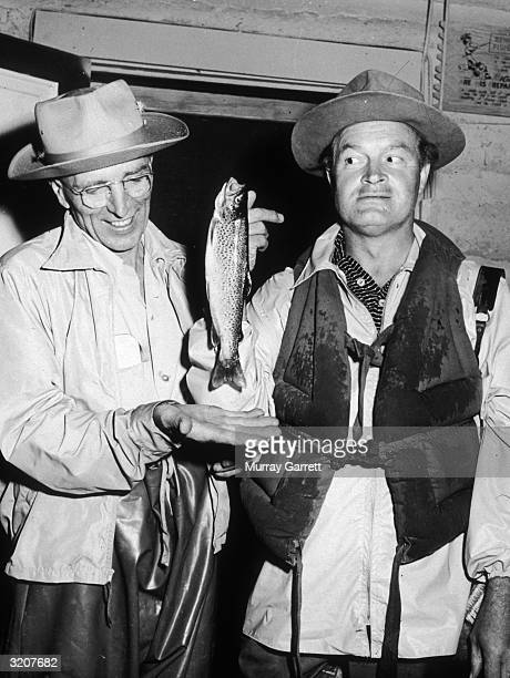 Britishborn comedian and actor Bob Hope displays a recently caught fish as an unidentified man holds his hand out below it on a Hope family vacation...