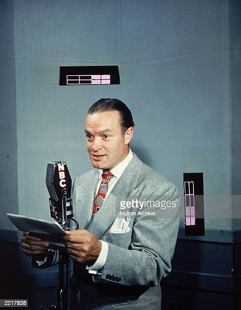 British-born comedian and actor Bob Hope speaks with a script at an NBC radio microphone, 1940s.