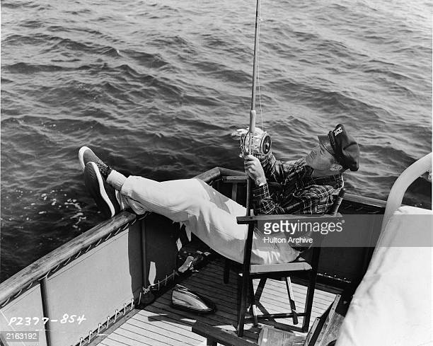 Britishborn comedian Bob Hope reclines as he fishes from the back of a boat wearing a nautical cap 1940s