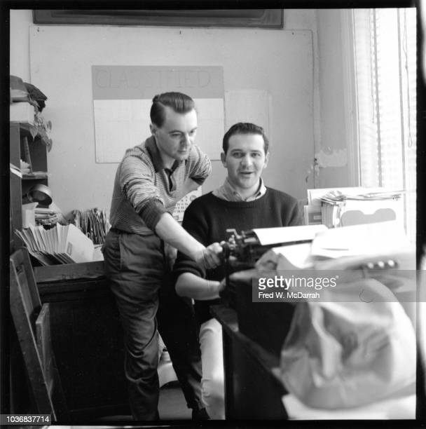 Britishborn journalist John Wilcock stands over the shoulder of writer Bill Manville in the office of the Village Voice newspaper New York New York...