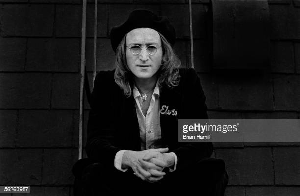 Britishborn singer and songwriter John Lennon dressed in a beret and coat with an attached Elvis pin kneels in front of a wall with his hands clasped...